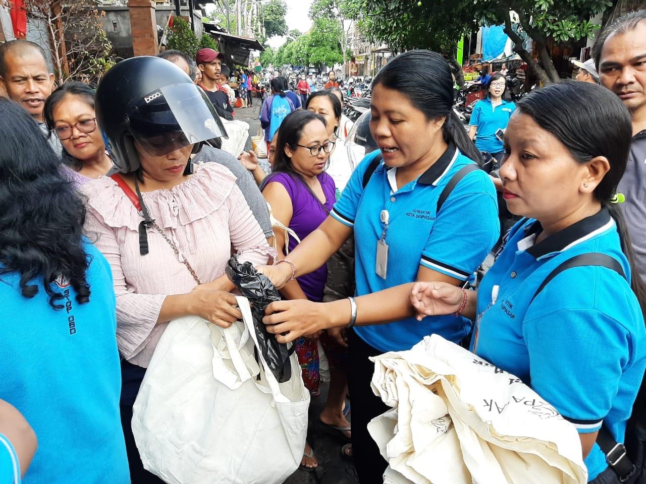 PEMBAGIAN tas ramah lingkungan kepada para pembeli di Pasar Ketapian, Denpasar Timur, Jumat (6/3/2020). Foto: istimewa.