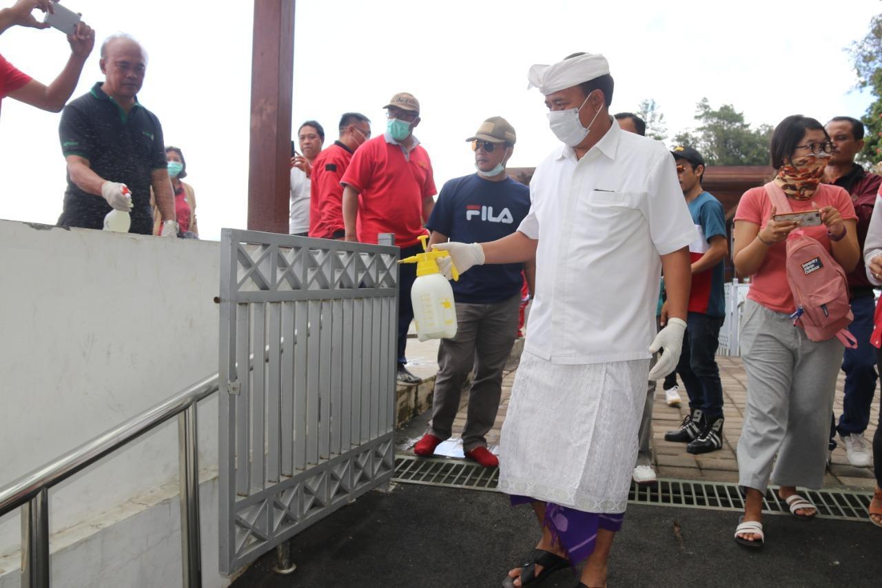 BUPATI Bangli, I Made Gianyar, saat melakukan gerakan serentak penyemprotan disinfektan di objek wisata Penelokan Kintamani, Minggu (15/3/2020). Foto: aan girinatha
