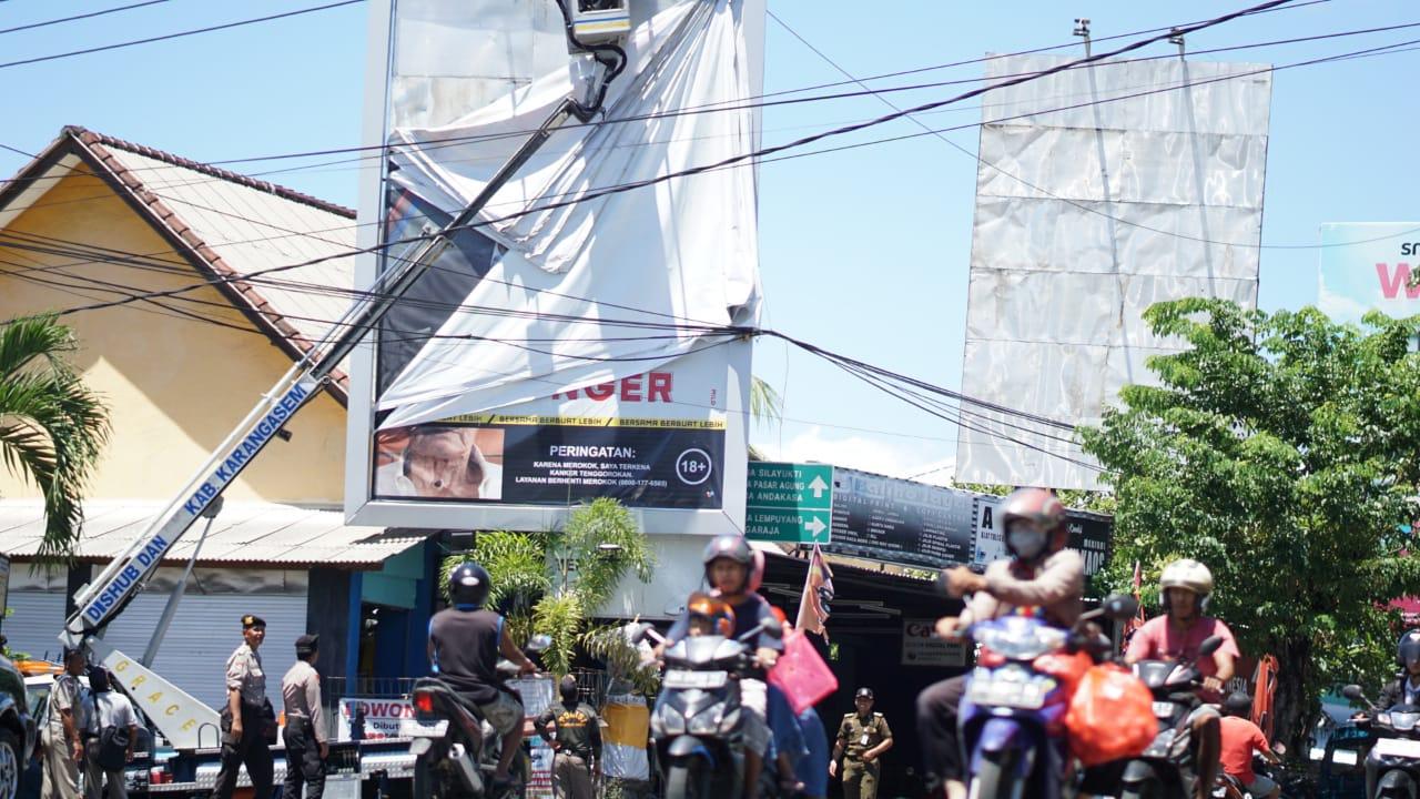 TIM Yustisi Kabupaten Karangasem saat menurunkan iklan rokok, Senin (16/3/2020). Foto: nengah adi suda dharma