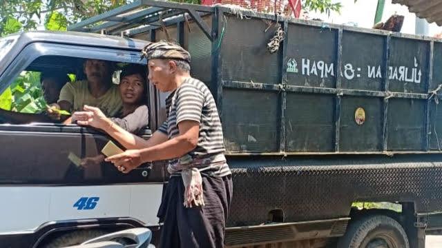 PETUGAS memungut uang retribusi pada salah satu mobil yang akan membuang sampah ke TPA Temesi. Foto: kadek adiputra wirawan