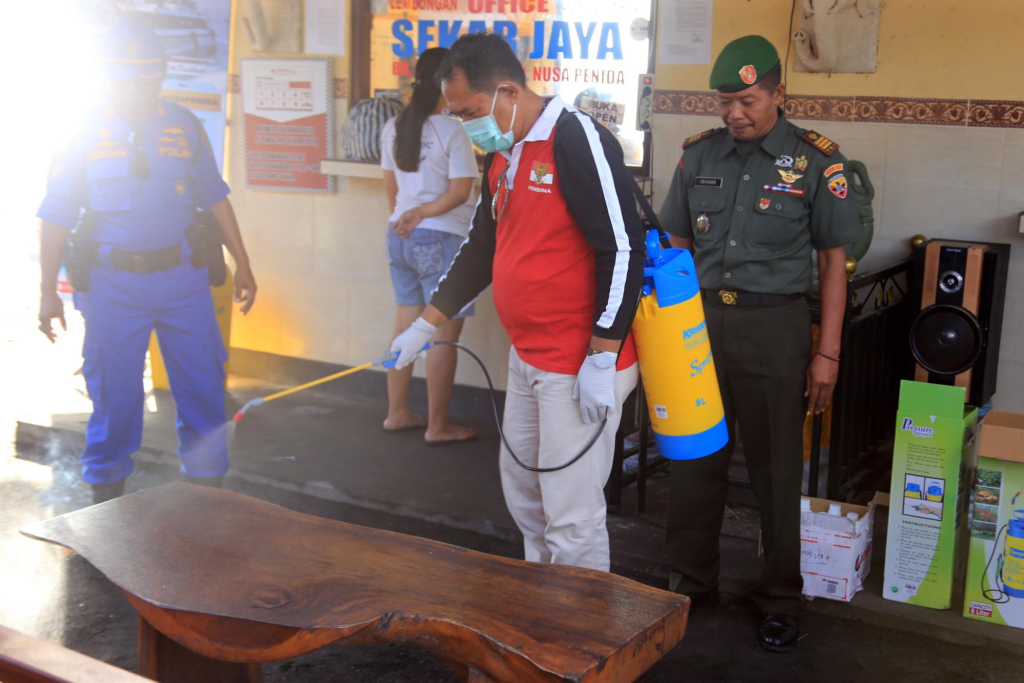 WABUP Klungkung, I Made Kasta, melakukan penyemprotan disinfektan di Pelabuhan Banjar Bias Kusamba, Minggu (15/3/2020). Foto: ketut bagus arjana