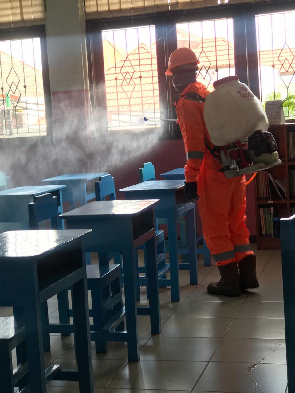 PETUGAS melakukan penyemprotan cairan disinfektan untuk mencegah penyebaran Virus Corona (Covid-19) di salah satu sekolah di Denpasar. Foto: istimewa