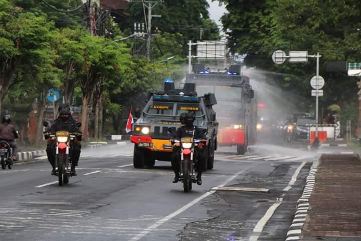 BRIMOB Polda Bali menggunakan mobil water cannon untuk menyemprotkan cairan disinfektan di Kota Denpasar, guna mencegah penyebaran virus Corona (Covid-19), Jumat (27/3/2020). Foto: istimewa