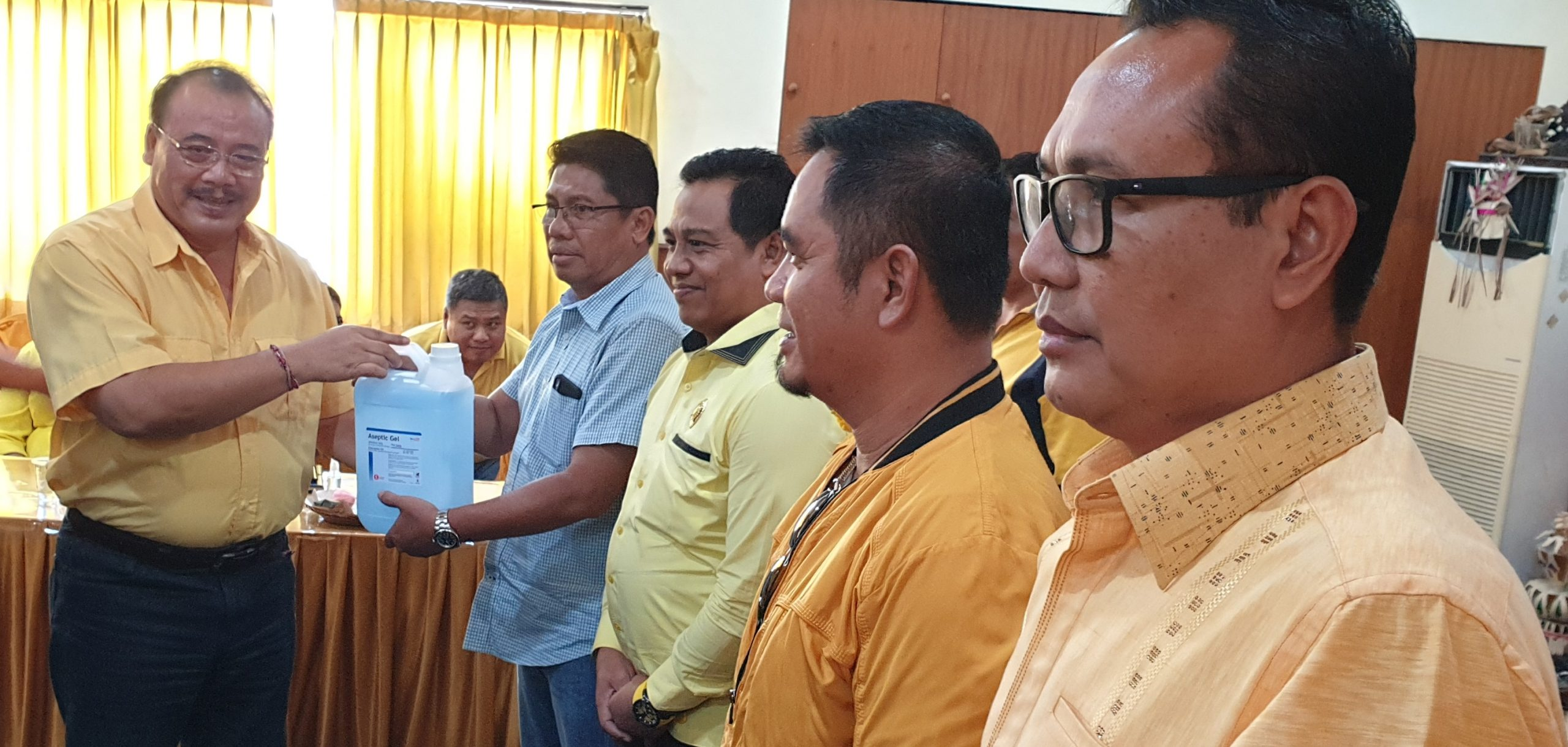 NYOMAN Sugawa Korry menyerahkan secara simbolis cairan sanitasi tangan kepada para ketua DPD Partai Golkar kabupaten/kota seluruh Bali, Minggu (15/3). Foto: gus hendra