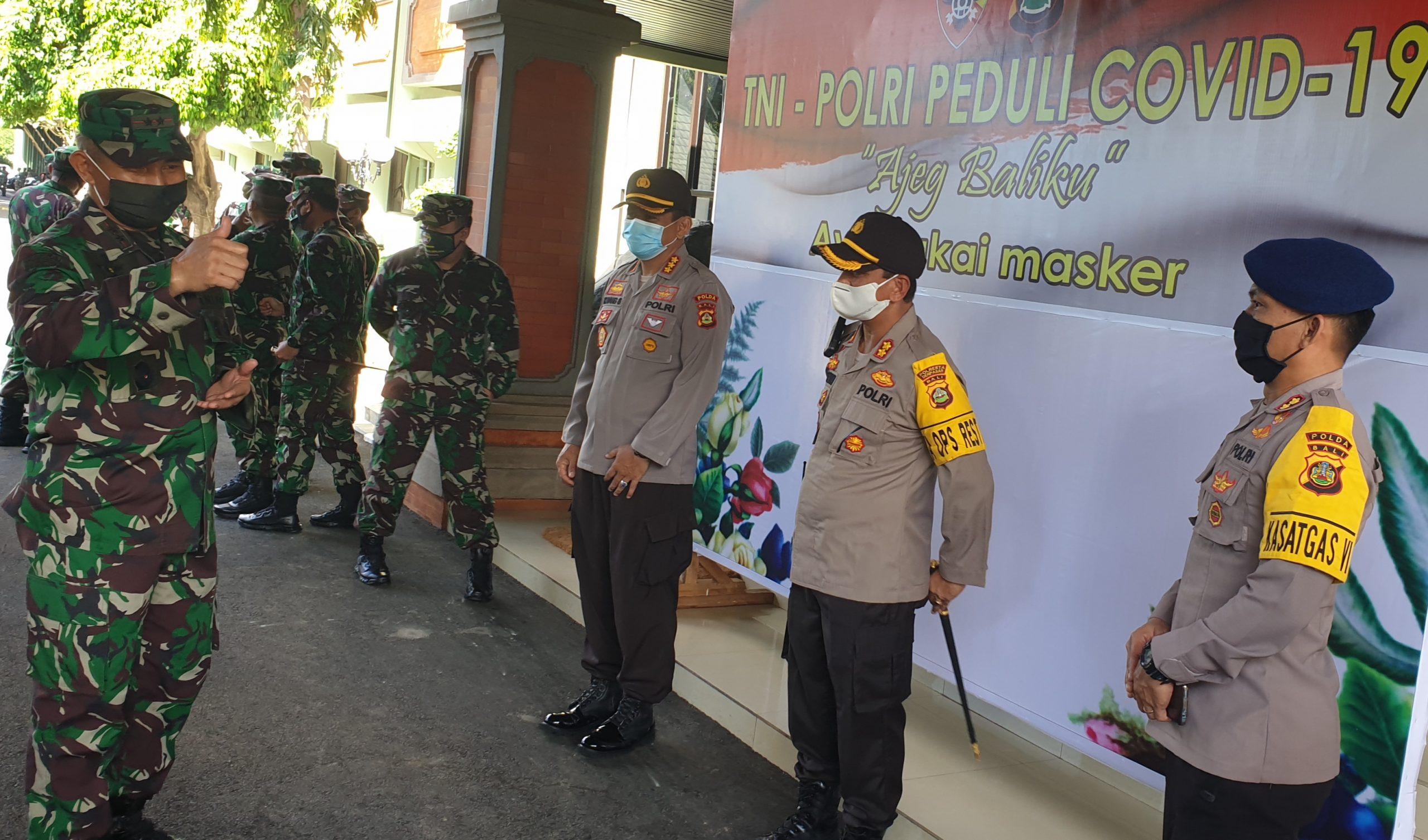 PANGDAM IX/Udayana, Mayjen TNI Benny Susianto, mengacungkan jempol saat berterima kasih kepada pejabat kepolisian yang hadir saat pembagian sembako untuk warga terdampak Covid-19, Kamis (23/4) lalu. Foto: gus hendra