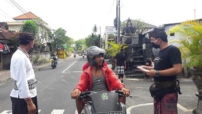 SATGAS Covid-19 Banjar Binoh Kaja, Desa Ubung Kaja, Denpasar, menyetop pengendara yang tidak memakai masker, lalu memberi sosialisasi dan masker, Minggu (26/4/2020). Foto: ist