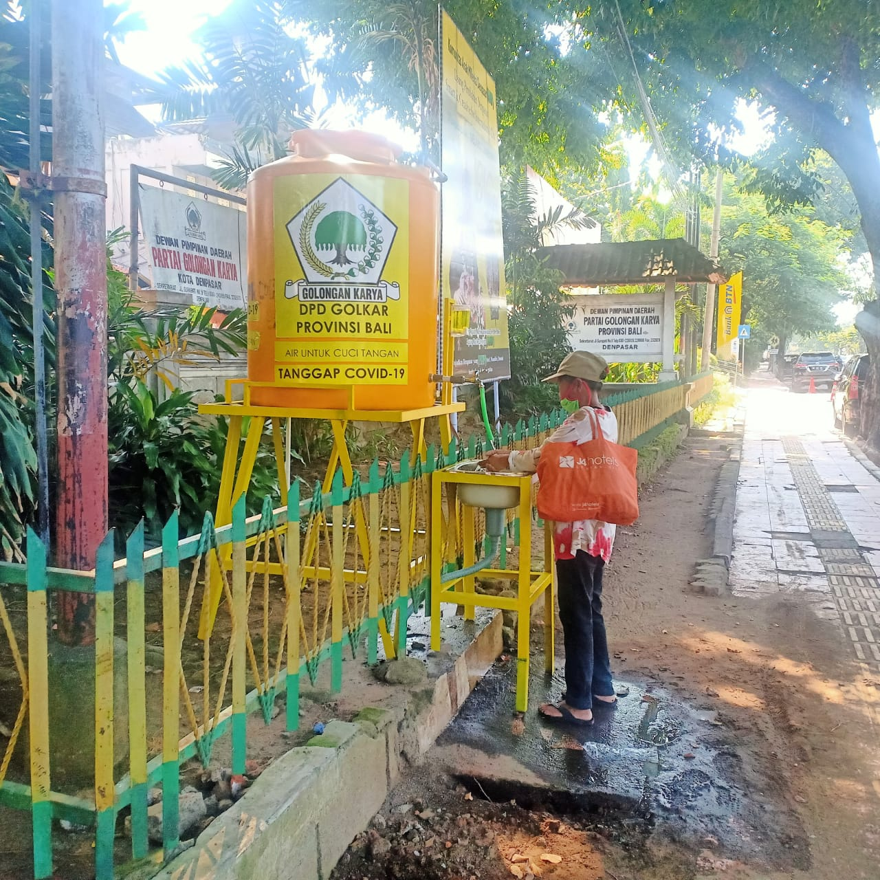 WARGA mencuci tangan dari tangki air yang dipasang di depan kantor DPD Partai Golkar Bali. Foto: ambros