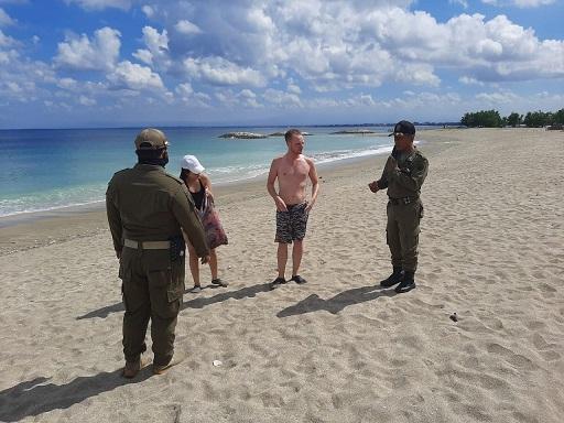 SATPOL PP BKO Kuta saat menegur wisatawan yang beraktivitas di Pantai Jerman. Foto: gay
