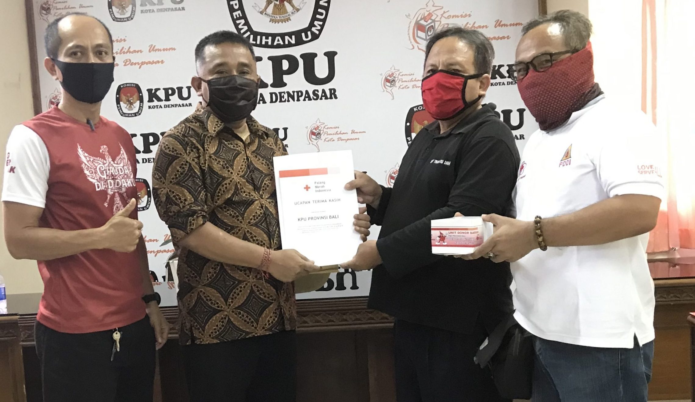 I Dewa Agung Lidartawan (dua kiri) saat menerima penghargaan dari PMI Bali atas kegiatan donor darah di KPU Denpasar, Senin (13/4/2020). Foto : gus hendra