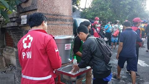 PALANG Merah Indonesia (PMI) melaksanakan berbagai upaya mencegah penyebaran Covid-19, seperti yang dilakukan di Pasar Sanglah, Rabu (22/4/2020). Foto: ist