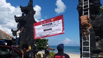 PETUGAS memasang spanduk peringatan penutupan kawasan Pantai Jimbaran untuk menghentikan penyebaran pandemi Covid-19. Foto: istimewa