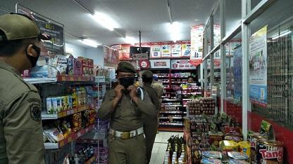 PETUGAS Satpol PP Buleleng melakukan sidak ke sejumlah toko modern dan warung yang masih buka di luar jam operasional pada Selasa (14/4) malam. Foto: ist