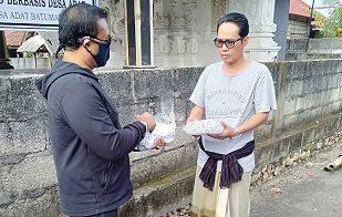 WAKIL Ketua DPRD Klungkung, Wayan Baru, S.Sos., memberikan masker kepada warga perdesaan di Nusa Penida untuk mencegah penularan Covid-19, Rabu (15/4/2020). Foto: ist