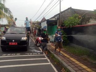 TOKOH masyarakat, I Putu Gede Menala Wisnawa yang juga anggota DPRD Kota Denpasar, turut turun melakukan penyemprotan disinfektan yang dilakukan Pemerintah Desa Penatih Dangin Puri, Minggu (5/4/2020). Foto: tra
