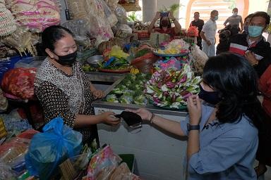KETUA K3S Denpasar, IA Selly Dharmawijaya Mantra menyerahkan bantuan masker kepada para pedagang Pasar Rakyat Pasar Badung. Foto: tra