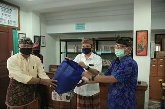 WALIKOTA Denpasar, IB Rai Dharmawijaya Mantra dengan tetap memperhatikan phyisical dan social distancing saat menyerahkan masker yang diterima Lurah Panjer, I Made Suryanata di Kantor Lurah Panjer, Kamis (9/4/2020). Foto: ist