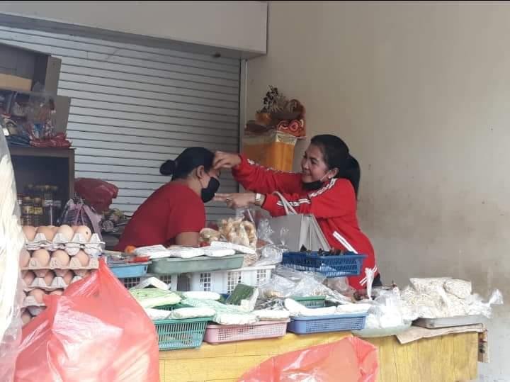 NI Made Ratnadi membagikan masker kepada pedagang di salah satu warung di wilayah Desa Blahbatuh. Foto: adi