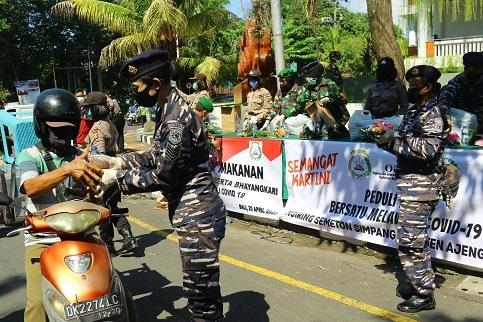 ANGGOTA TNI tampak memberikan nasi bungkus kepada warga yang melintas di Gedung Dharma Negara Alaya Pemerintah Kota Denpasar, Jalan Mulawarman No.1 Lumintang, Denpasar Utara, Senin (20/04/2020) siang. Foto: alt