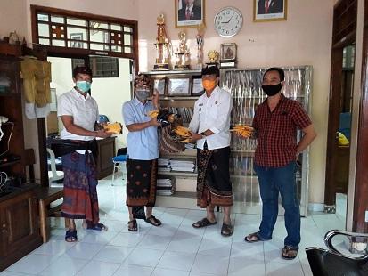 WAKIL Ketua DPRD Karangasem, I Nengah Sumardi menyerahkan sumbangkan masker ke warga desa Bugbug, Kamis (23/4/2020). Foto: ist