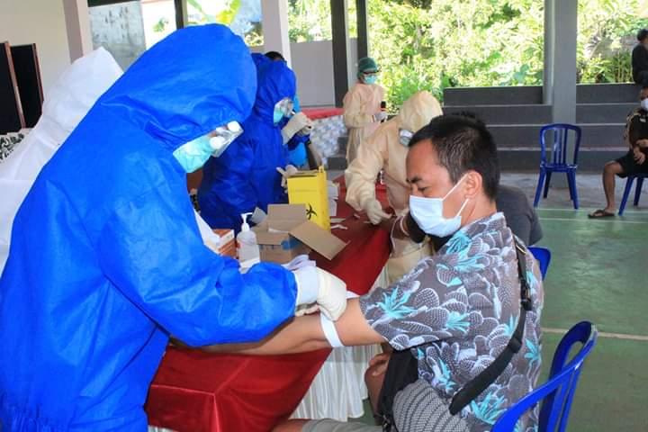 PENGAMBILAN Sampel yang dilakukan petugas medis Puskesmas Tejakula II mengenakan APD lengkap terhadap beberapa PMI dari Desa Bondalem saat tes cepat. Foto: arik