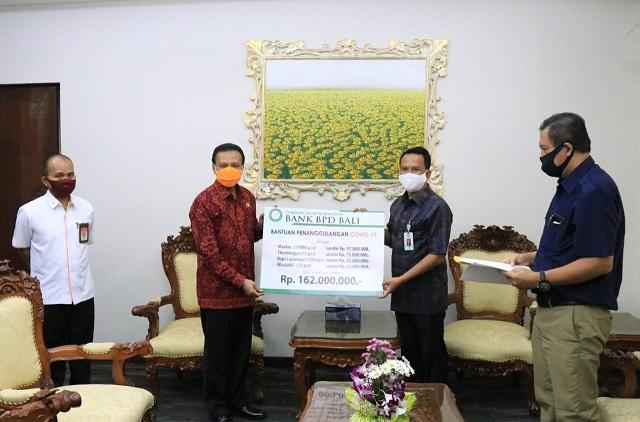 KETUA Harian Gugus Tugas Percepatan Penanganan Covid-19 Provinsi Bali, Dewa Made Indra, saat menerima bantuan dari BPD Bali dan PNB. Foto: ist