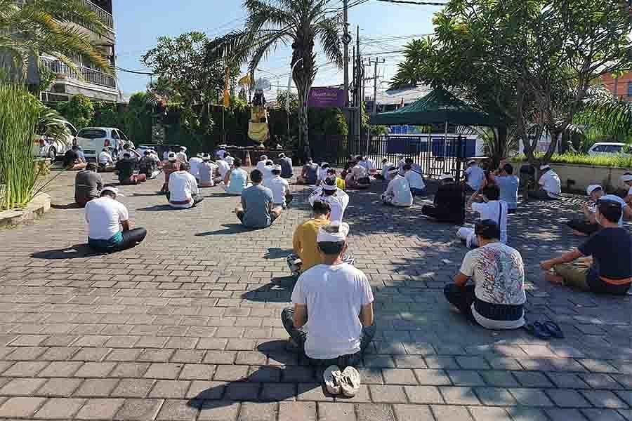 PARA PMI asal Denpasar mengikuti persembahyangan bersama Tilem Kedasa, Rabu (22/4/2020) di tempat karantina. Foto: ist