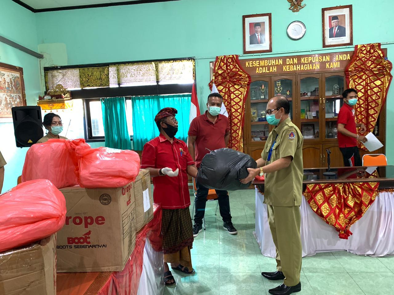 COKORDA Gede Agung (mengenakan udeng) didampingi Ketua DPC PDIP Klungkung, AA Gede Anom, saat menyerahkan bantuan pakaian APD, masker, dan pembersih tangan ke instalasi medis di Klungkung, Senin (13/4/2020). Foto: Ist