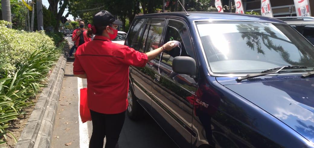 SKUAT Sarinah dari Tim Gotong Royong Penanggulangan Covid-19 DPD PDIP Bali saat membagikan masker, pembersih tangan, dan jamu herbal untuk masyarakat di seputar Sanur, Densel, Sabtu (18/4/2020). Foto/Ist