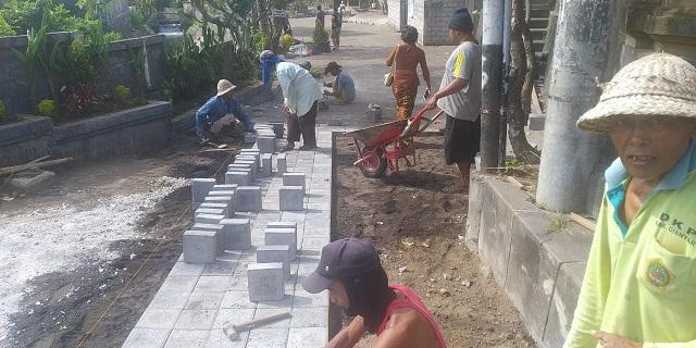 WARGA mengerjakan proyek PKT Penataan dan Pavingsasi Lingkungan Permandian Umum di Banjar Kesian, Desa Lebih. Foto: adi