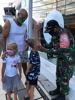 SALAH seorang wisatawan saat diberikan masker dalam sosialisasi penggunaan wajib masker Desa Adat Seminyak. Foto: gay