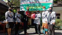 KETUA Cabang PGRI Dentim, Wayan Darsana, didampingi para pengurus disaksikan Ketua PGRI Kota Denpasar, I Nyoman Winata, menyerahkan paket sembako kepada tenaga kependidikan. Foto: alt