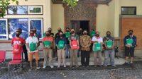 ANGGOTA Pena-NTT di Bali menerima bantuan sembako dari Indonesia Power Unit Bali di halaman kantor Ombudsman Perwakilan Provinsi Bali Jalan Melati No.6 Kereneng Denpasar, Sabtu (30/5). Foto: ist