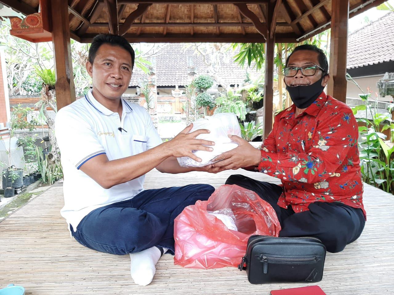 COKORDA Gede Agung (kanan) menyerahkan bantuan masker dan pembersih tangan untuk warga yang diterima Camat Dawan, AA Gde Wedana, Selasa (19/5/2020). Foto:Ist