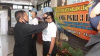Foto: MPLS TIGA KEPALA SMK PGRI 3 Denpasar, Nengah Madiadnyana, membuka MPLS secara virtual, Senin (13/7), ditandai penyematan tanda MPLS pada perwakilan siswa baru. Foto: ist