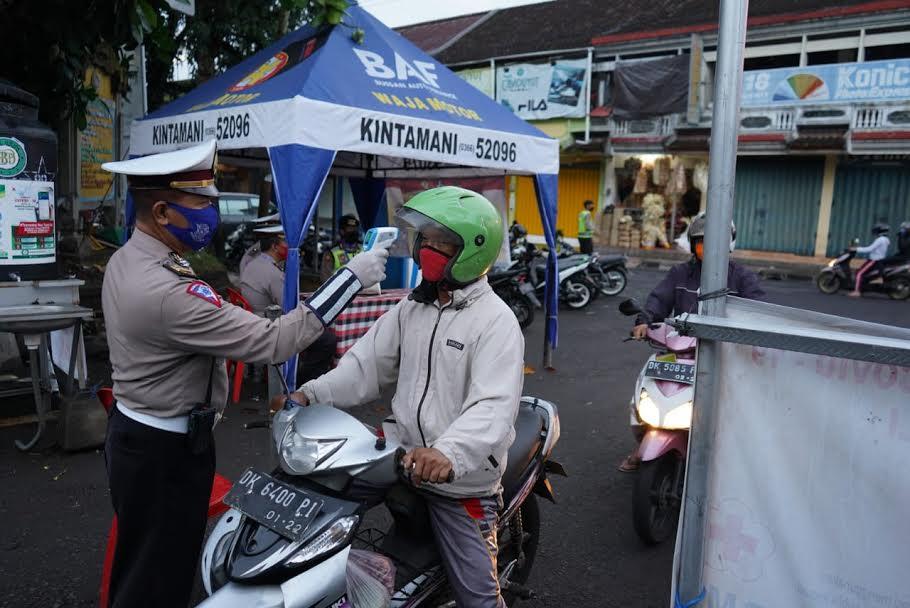 Foto: PASAR KIDUL PERSONEL kepolisian mengecek suhu pengunjung Pasar Kidul. Kini setiap pengunjung Pasar Kidul wajib mematuhi protokol kesehatan. Foto: gia