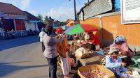 Foto : POLISI MASKER PERSONEL Polres Klungkung membantu memasang masker kepada warga lansia yang berkunjung ke Pasar Desa Satria, Kecamatan Klungkung, Minggu (5/7). Foto: baw