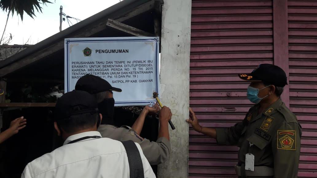 Foto: SATPOL PP SEGEL SATPOL PP Gianyar ketika memasang papan segel di usaha tahu tempe milik Erawati di Lingkungan Sema, Desa Bitera, Gianyar, Rabu (19/8) lalu. Foto: adi