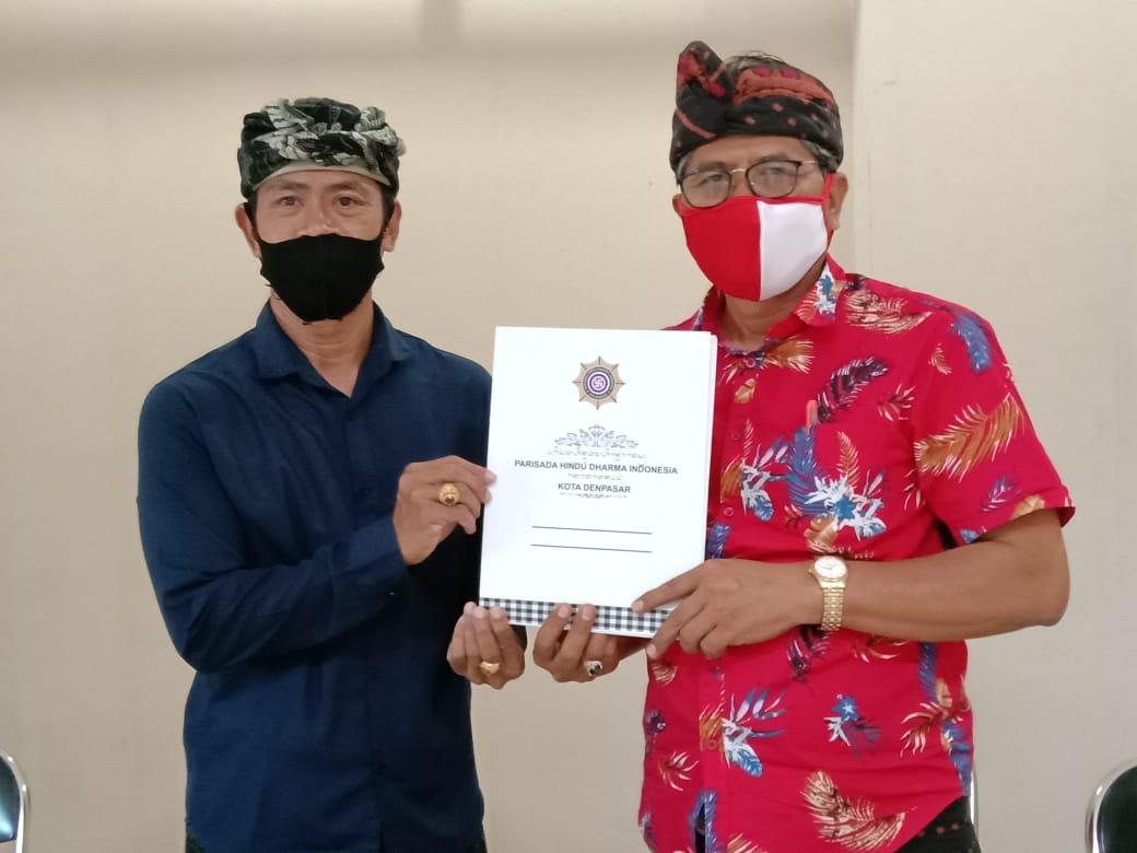 KETUA PHDI Kota Denpasar, I Nyoman Kenak, dan Bendesa Madya MDA Kota Denpasar, AA Ketut Sudiana, menunjukkan Imbauan Bersama setelah ditandatangani, Sabtu (1/8). Foto: rap