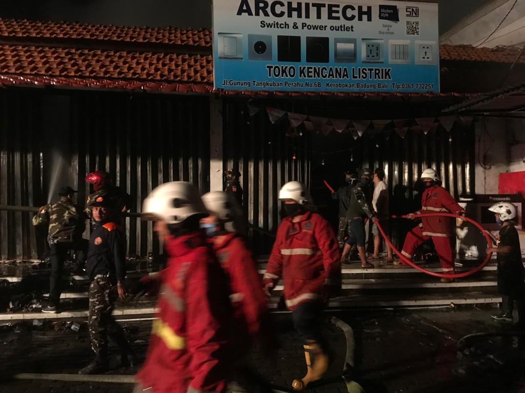 PETUGAS pemadam kebakaran melintas di depan toko Kencana Listrik yang terbakar, dengan situasi di latar belakang upaya pemadaman api yang dibantu anggota Banser Kuta Utara. Foto: gus hendra