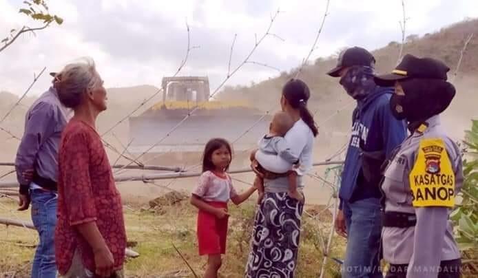 Foto : APARAT kepolisian tengah berkomunikasi dengan warga yang masih tinggal bersama anaknya di atas di lahan Sirkuit MotoGP yang mulai dilakukan penggusuran. Foto: rul