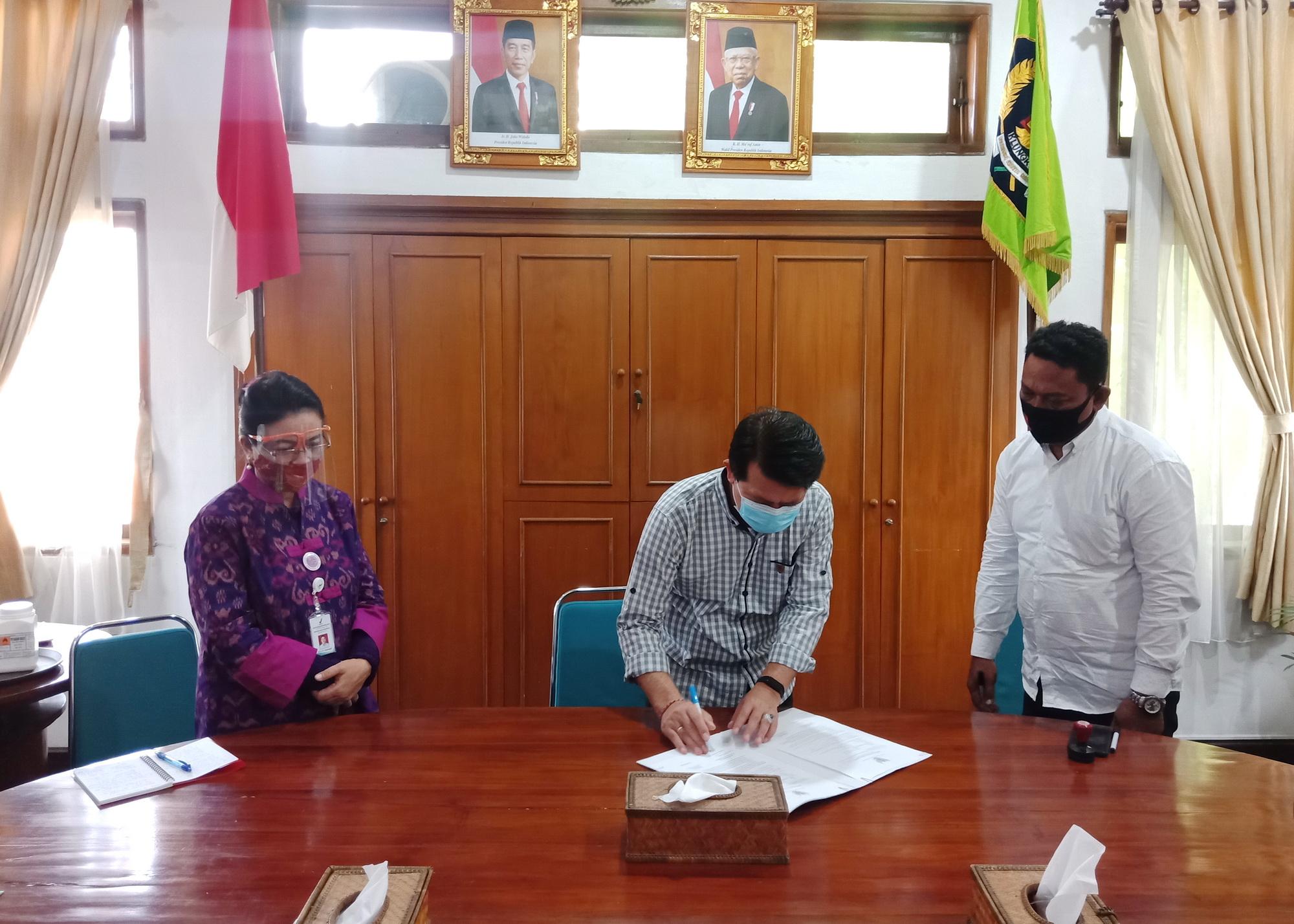 BUPATI Suwirta melakukan tanda tangan penyerahan bantuan KIO3 di Ruang Rapat, Kantor Bupati Klungkung, Selasa (29/9/2020). Foto: baw