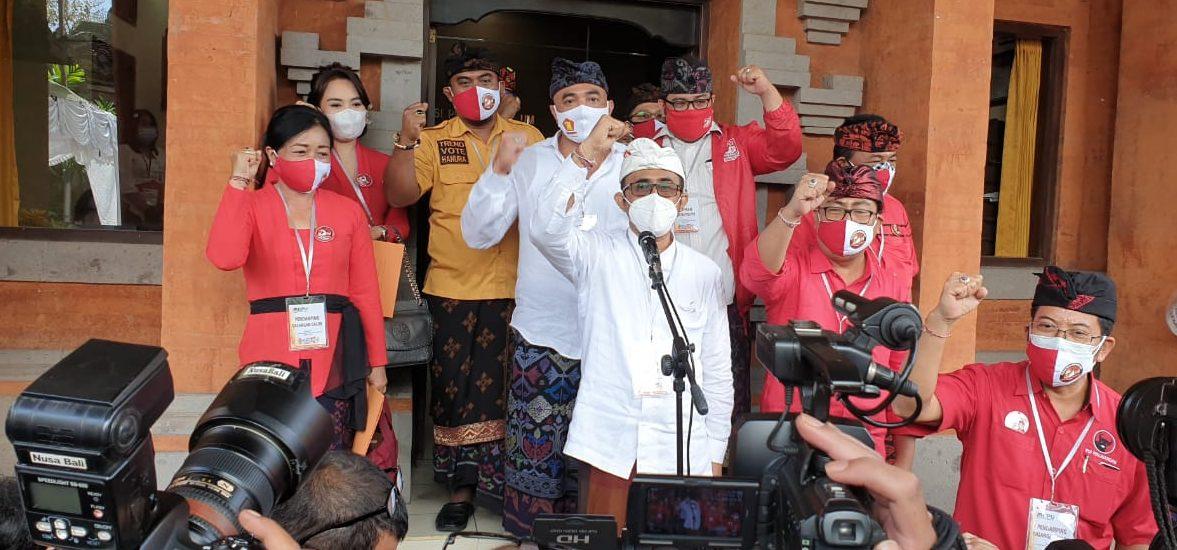 """IGN Jaya-Negara (depan mik) didampingi Kadek Agus Arya Wibawa memekikkan """"merdeka"""" usai mendaftar di KPU Denpasar, Jumat (4/9/2020). Foto: gus hendra"""