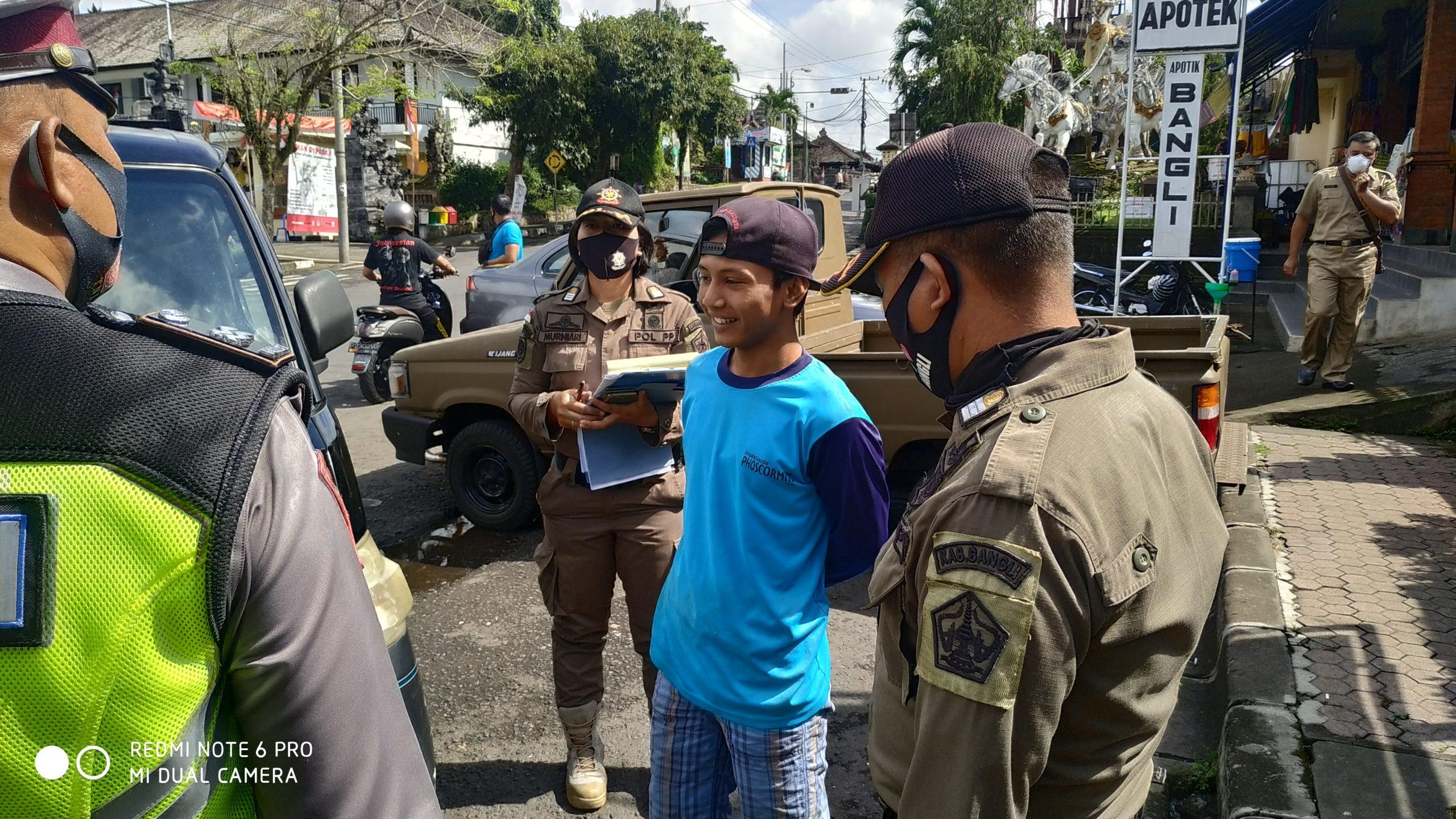 Foto: TAK GUNAKAN MASKER PETUGAS memberi teguran pada warga yang tak menggunakan masker di Bangli, Senin (7/9). Foto: gia