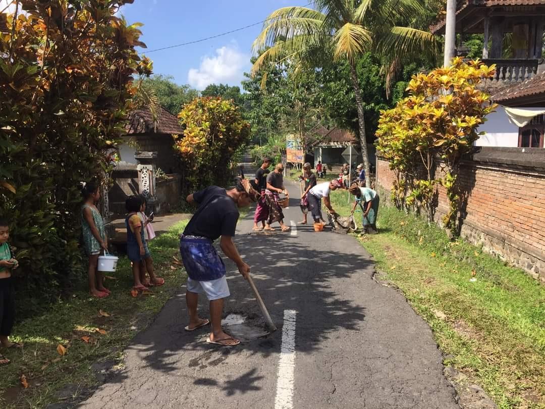 Foto: Warga Tambal jalan WARGA Dusun Waliyang, Abang, Karangasem melakukan penambalan jalan rusak secara swadaya pada Minggu (30/8). Foto: nad