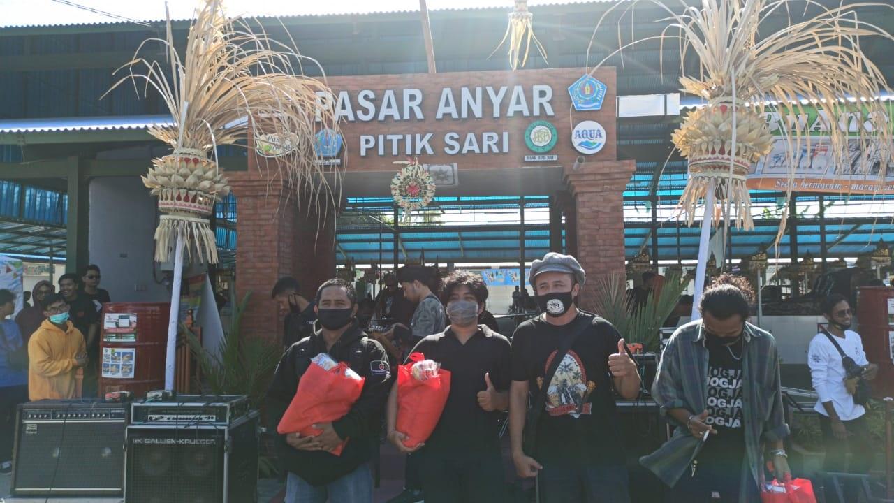 PENYERAHAN bantuan sembako pada peringatan HUT ke-7 Paguyuban JBT13 di lapangan parkir Pasar Anyar Pitik Sari, Pedungan, Minggu (13/9). Foto: ist