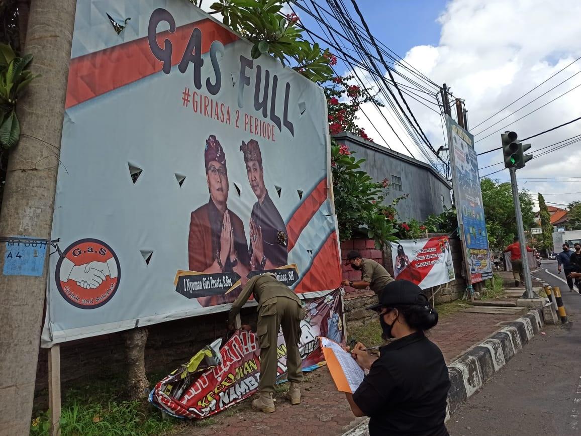 SATPOL PP Badung melakukan penertiban baliho pasangan calon yang dipasang sebelum masa kampanye. Foto: ist