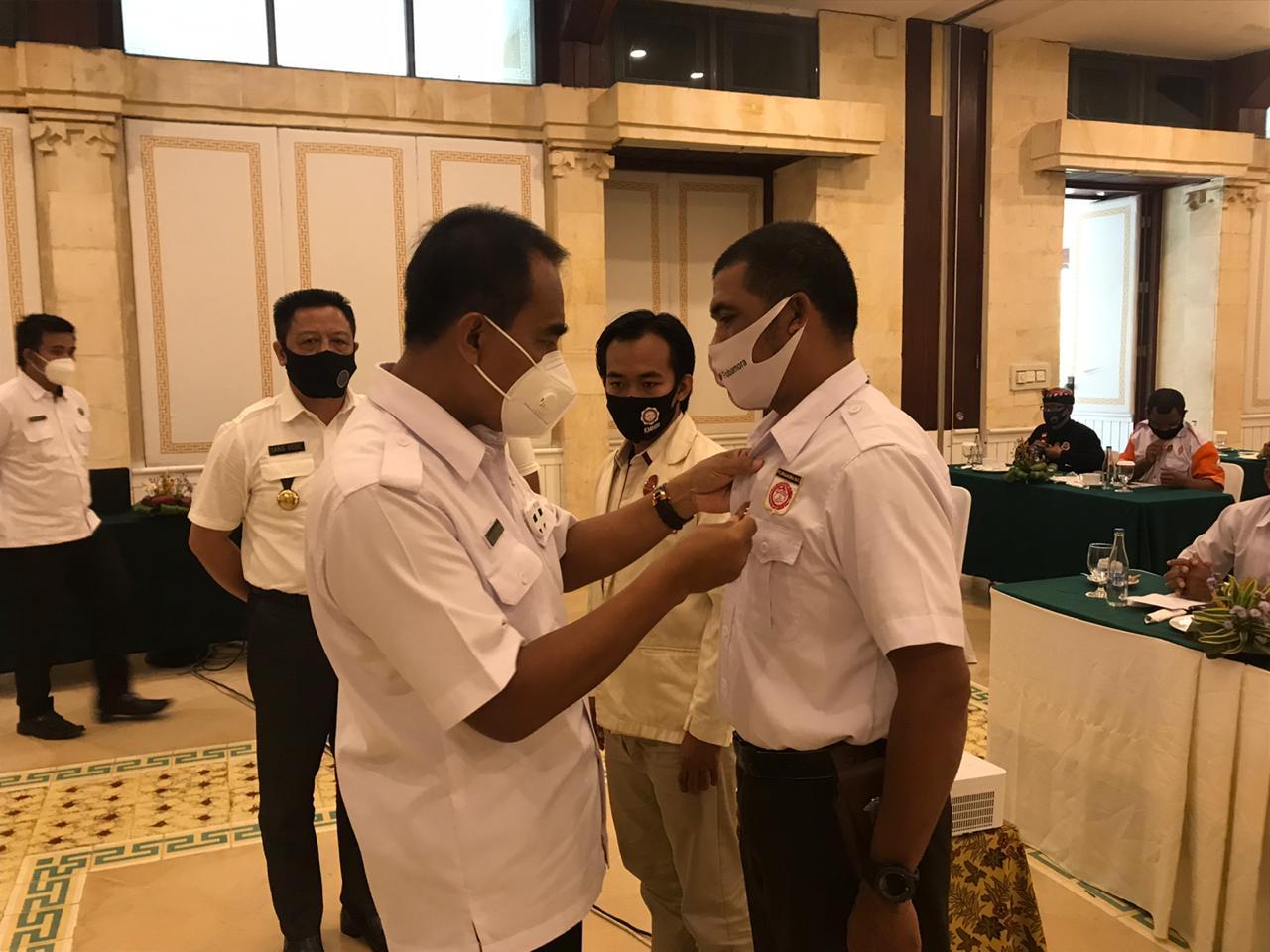 KEPALA BNNP Bali Brigjen Pol. Drs. I Putu Gede Suastawa, menyematkan tanda peserta pengembangan kapasitas P4GN (workshop) di lingkungan masyarakat yang diikuti para tokoh agama dan masyarakat di Kota Denpasar. Foto: ist
