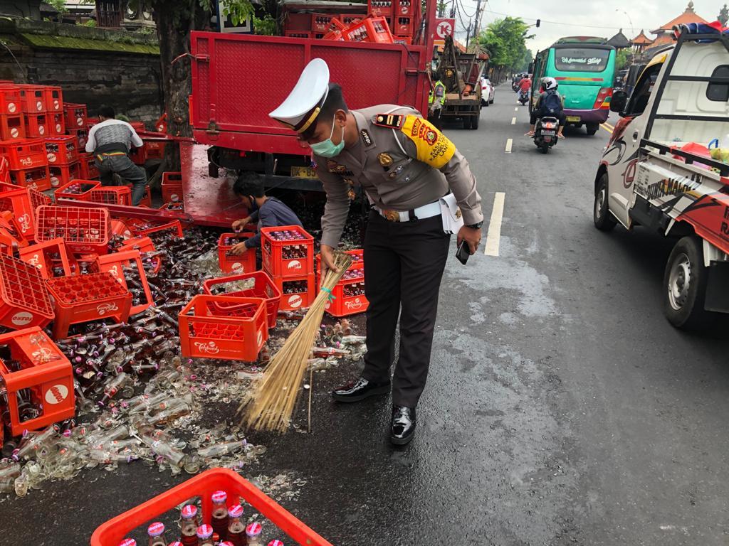 POLISI membersihkan sisa pecahan botol teh Sosro yang tumpah di Jalan Raya Kapal tepatnya di simpang Muncan, Mengwi, Jumat (23/10/2020) pagi. Foto: 020