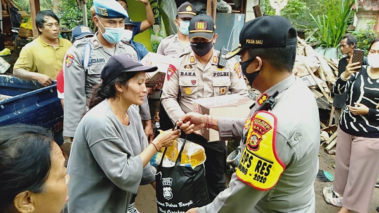 KAPOLRES Bangli, AKBP I Gusti Agung Dhana Ariawan, memberi bantuan berupa paket sembako kepada tiga KK yang terdampak tanah longsor. Foto: ist