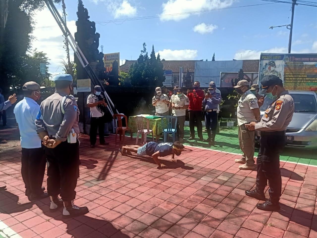 SATU warga yang terjaring operasi yustisi di Susut diganjar sanksi fisik push up. Foto: gia